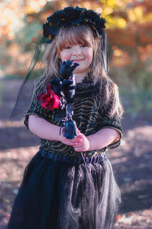 Little girl dressed up as a Halloween bride with red and black roses.