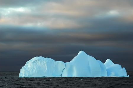 Blue iceberg with a dark sky Stock Photo