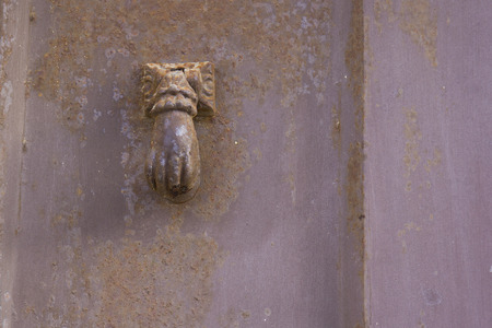 doorknocker: Old and corroded metal door knocker shaped by hand.