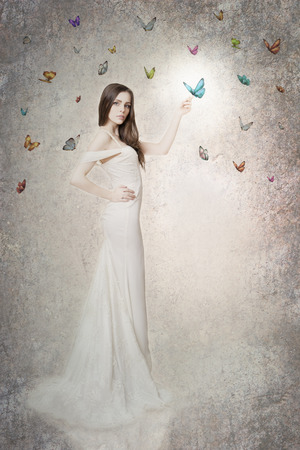 Studio portrait of a young beautiful bride in a white dress with butterflies. Professional make-up and hairstyle. Vintage style. photo