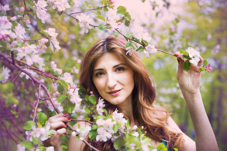 Young beautiful girl in spring blooming gardens photo