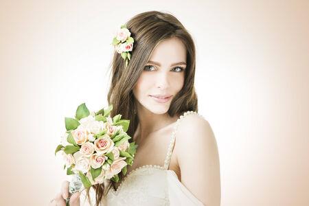 Estudio de retrato de una joven y bella novia con un ramo de boda. Maquillaje profesional y peinado. photo