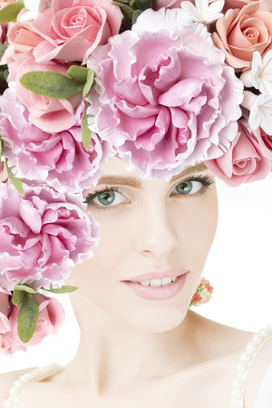 Portrait of beautiful young girl with flowers. Peonies and roses closeup. Studio shot. photo