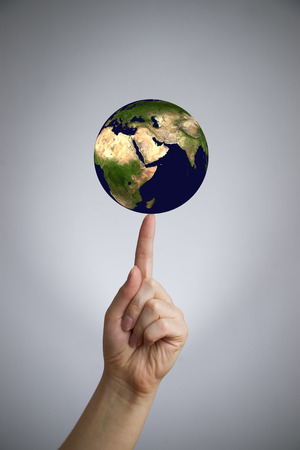 The Earth in a female hand on the index finger.  photo