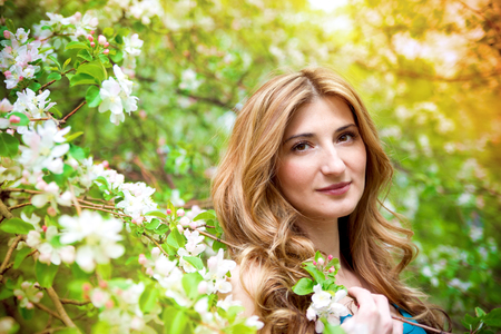Beautiful young woman in blossoming garden. photo