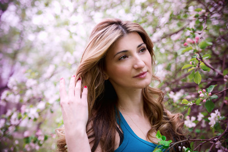 Beautiful young woman in blossoming garden   photo