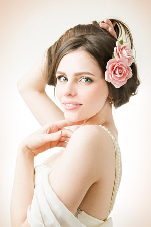 Studio portrait of a young beautiful bride in a white dress. Professional make-up and hairstyle with flowers. photo