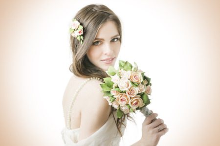 Studio portrait of a young beautiful bride with a wedding bouquet. Professional make-up and hair-style. photo