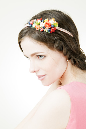 Studio portrait of a young beautiful woman with flower wreath on head. Make-up and hairstyle with flowers. photo