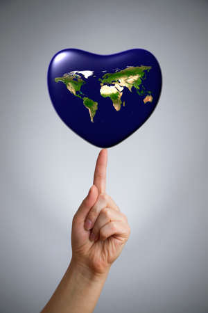 The Earth in the shape of heart in a female hand on the index finger. Gray background. 3D render. photo