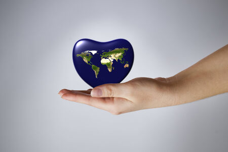 The Earth in the shape of heart in a female hand. Gray background. 3D render. photo