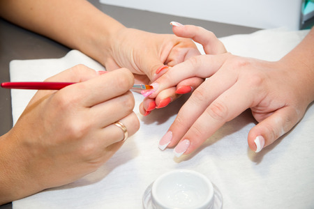 Artificial nails in a beauty salon  Hands close-up  The process of nails  photo