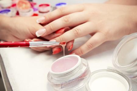 ビューティー サロンの手のクローズ アップで人工爪の爪のプロセス