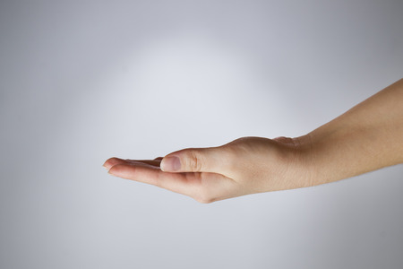 Female hand on a gray background. Empty outstretched palm. Copy space photo