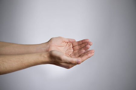 Male hands on a gray background. Empty outstretched palm. Copy space photo