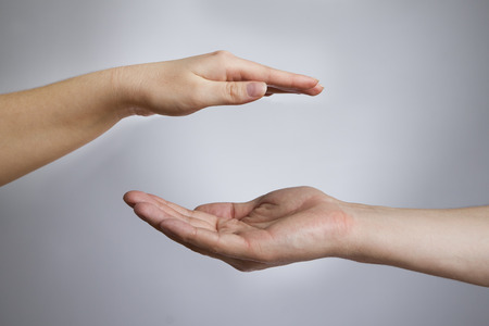 open space: Male and female hands on a gray background  Empty outstretched palm  Copy space