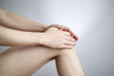 Knee pain in men on gray background photo