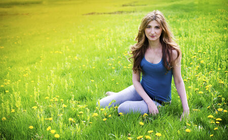 Beautiful young girl resting in meadow photo
