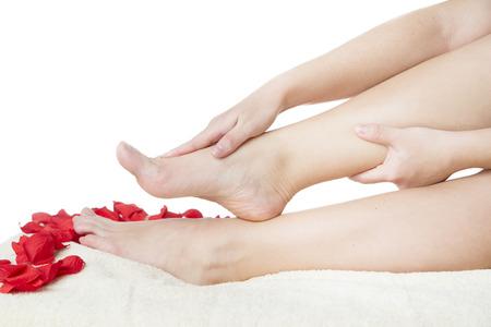 Beautiful female feet and rose petals. photo