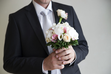 Wedding bouquet in hands of groom. photo