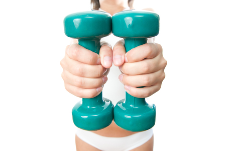 Girl with green dumbbells in hand, isolated on a white background. photo