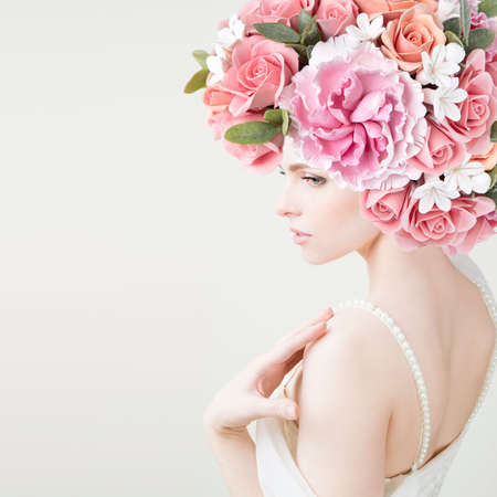 Portrait of beautiful young girl with flowers  Peonies and roses closeup  Studio shot  photo