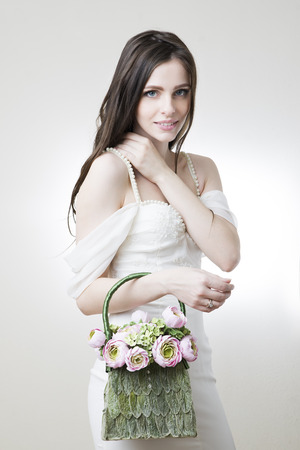 Studio portrait of a young beautiful bride with her handbag in her hand  Professional make-up and hairstyle  photo