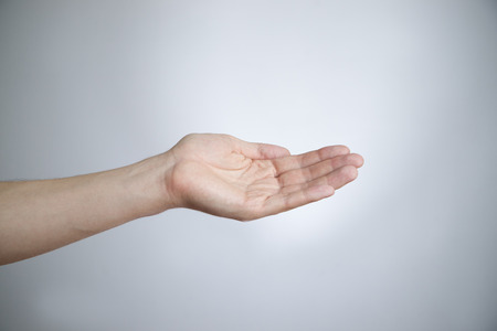 Male hand on a gray background  Empty outstretched palm  Copy space photo