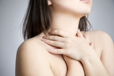 Sore throat of a women  Touching the neck photo