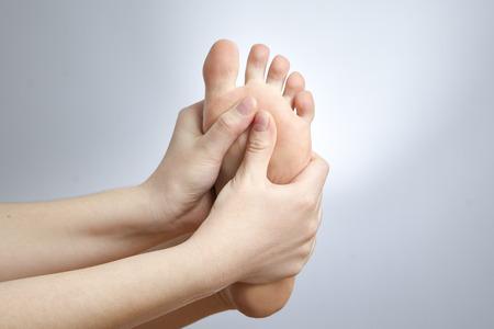 manos y pies: Dolor en el pie Masaje de pies femeninos pedicura Foto de estudio sobre un fondo gris Foto de archivo