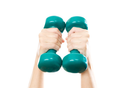 Green dumbbells in female hands isolated on white background. photo