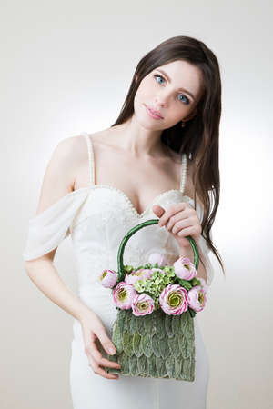 Studio portrait of a young beautiful bride with her handbag in her hand. photo