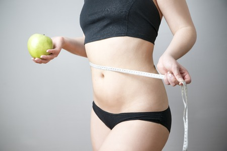 Green apple in female hands on gray background. Body care. Weight loss, diet Stock Photo