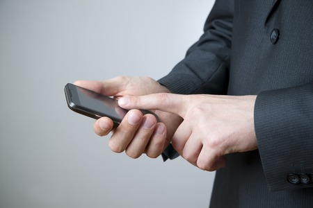 Modern mobile phone in male hand. Businessman using smartphone photo