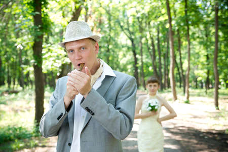 Wedding: beautiful young bride and groom standing in a park. photo