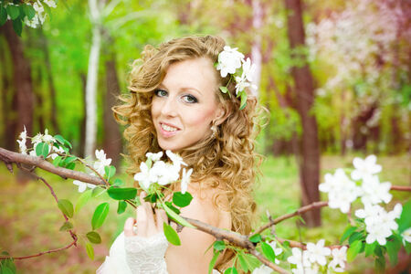 Beautiful bride in a white dress in blooming gardens in the spring. Professional make-up and hairstyle. photo
