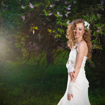 Beautiful bride in a white dress on a lilac background in spring. Professional make-up and hairstyle. photo