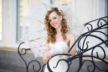 Beautiful bride in white dress with umbrella photo