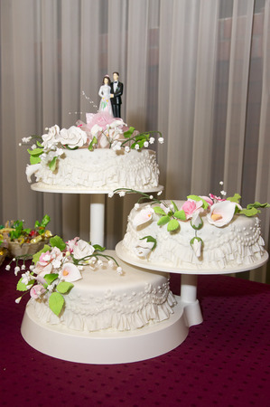 Beautiful tasty three-tiered wedding cake with roses of cream. photo