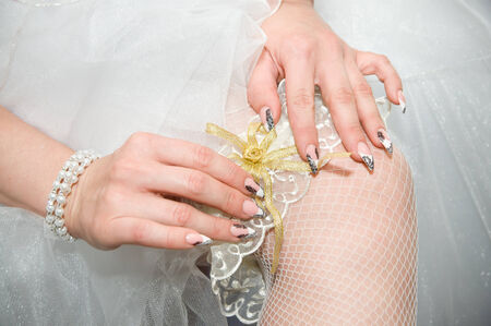 White garter bride on foot. Wedding manicure. photo