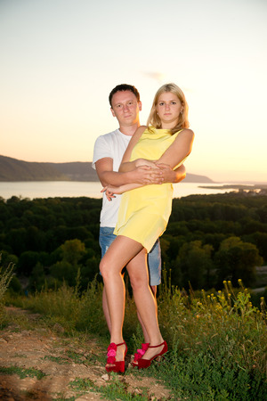 Loving couple at sunset in summer. Young man and woman on the nature. photo