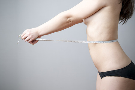 Female body with measuring tape on gray background. Weight loss, diet photo