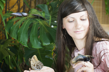 Portrait of beautiful girl with butterfly in a greenhouse photo