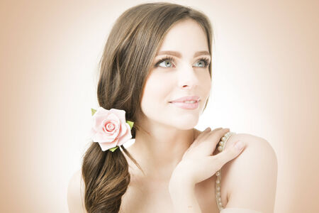 Studio portrait of a young beautiful bride. Professional make-up and hairstyle with flowers. photo