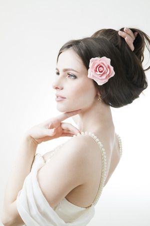Studio portrait of a young beautiful bride in a white dress. Professional make-up and hairstyle with flowers.