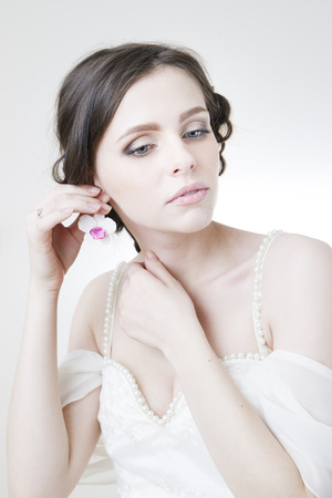 Studio portrait of a young beautiful bride in a white dress. Professional make-up and hairstyle. photo