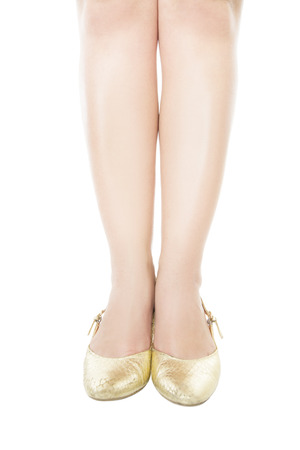 Slender legs gold shoes isolated on white background photo