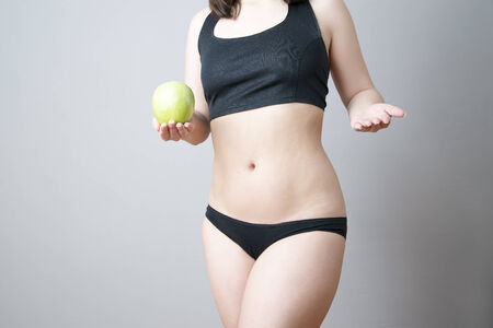 Female body with green apple on gray background. Weight loss, diet photo