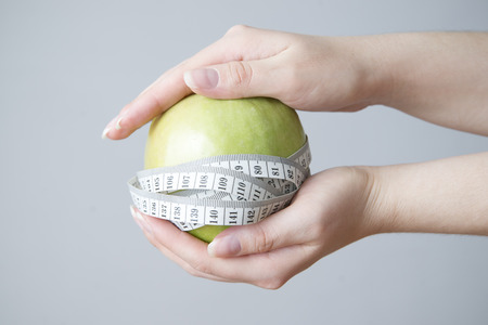 Green apple in female hands on gray background. Weight loss, diet photo