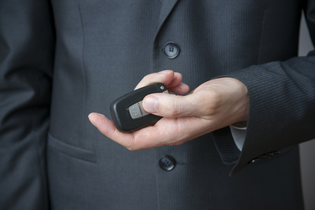 Businessman using car key. Keyless in male hand photo